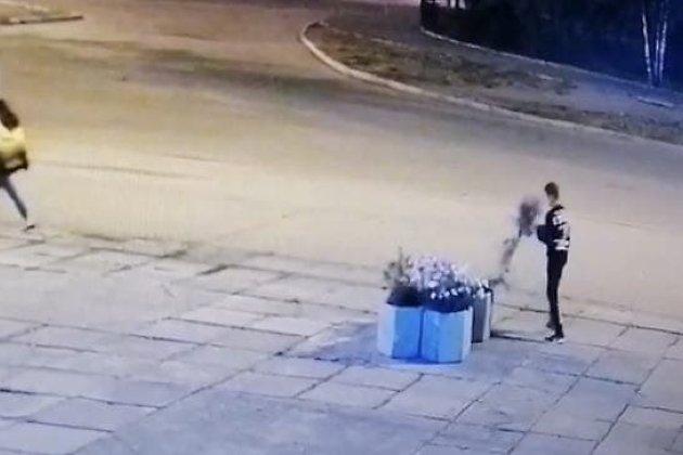 Юноша вырвал охапку цветов из городского вазона
