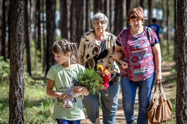 Девочка несёт цветы на могилу прадеда