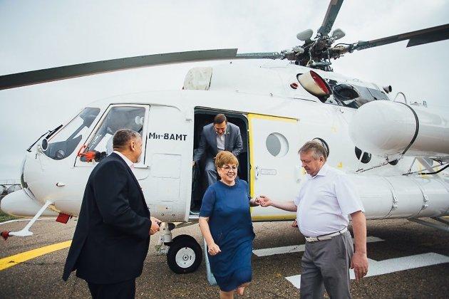 Первый замминистра здравоохранения края Иван Шовдра помогает губернатору Наталье Ждановой спуститься с трапа.
