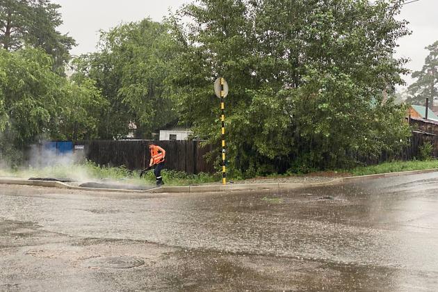 Работник укладывает асфальт во время дождя по улице Кочеткова в Чите
