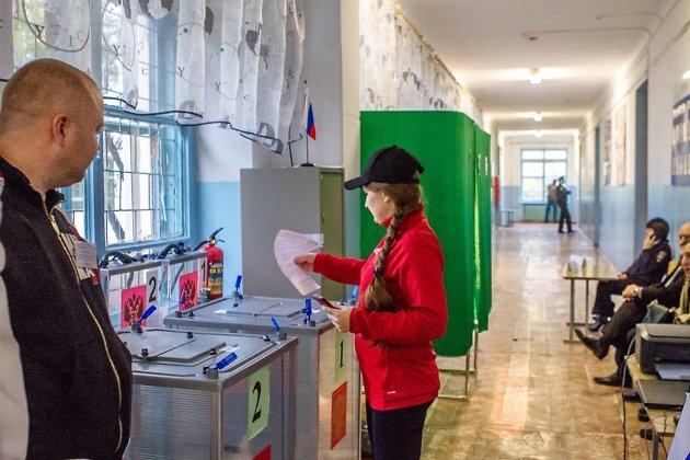 Избирательница на участке №410 опускает бюллетень в урн для голосования