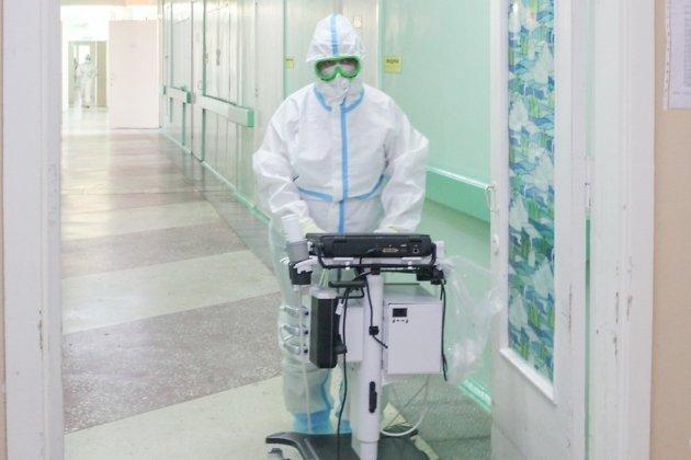 В госпитале имеется вся необходимая техника для лечения больных коронавирусом. Здесь изображён врач с мобильным аппаратом УЗИ