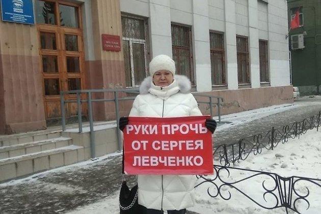Ольга Носенко с плакатом возле здания, где размещаются городские отделения