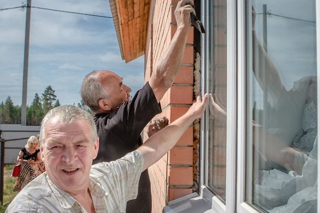 Руководитель службы единого заказчика Анатолий Серёгин осматривает неправильно установленный стеклопакет. Из-за такого окна внутри дома образовывается конденсат,  и стены покрываются плесенью