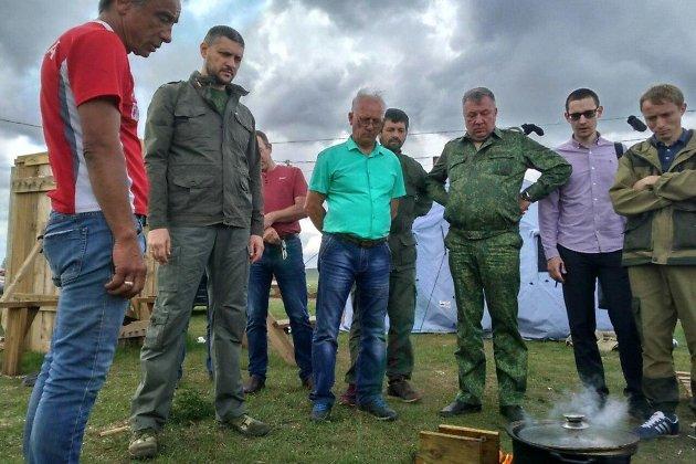 Врио губернатора Забайкалья Александр Осипов (второй слева) проверяет пропитанный огнеупорной жидкостью брус. Тасырхой