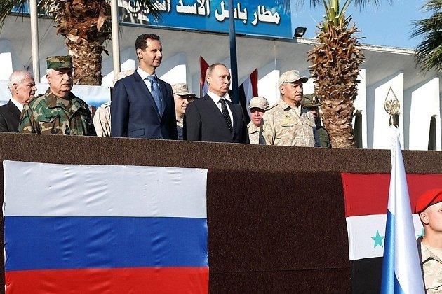 Президент России Владимир Путин во время посещения авиабазы Хмеймим в Сирии. С президентом Сирии Башаром Асадом (слева) и министром обороны России Сергеем Шойгу (справа).